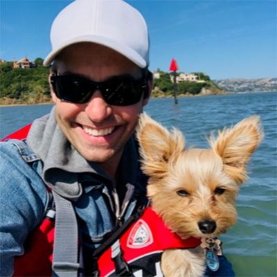 Peer Support Volunteer Eric Lindroos and Dog in life vests on the water